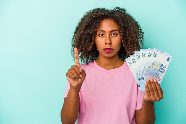 Young african american woman holding euro banknotes isolated on blue background showing number one with finger.