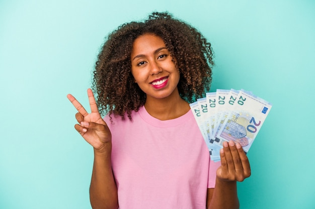 Young african american woman holding euro banknotes isolated on blue background showing number two with fingers.