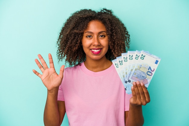 Young african american woman holding euro banknotes isolated on blue background smiling cheerful showing number five with fingers.