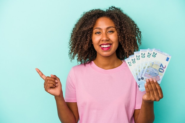 Young african american woman holding euro banknotes isolated on blue background smiling and pointing aside, showing something at blank space.