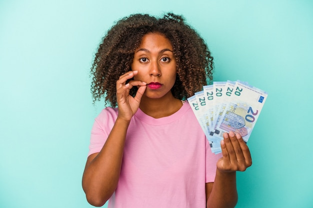 Young african american woman holding euro banknotes isolated on blue background with fingers on lips keeping a secret.