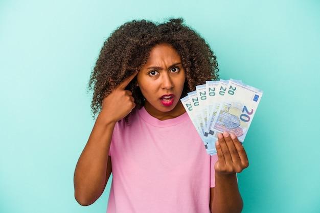 人差し指で失望のジェスチャーを示す青い背景に分離されたユーロ紙幣を保持している若いアフリカ系アメリカ人女性。