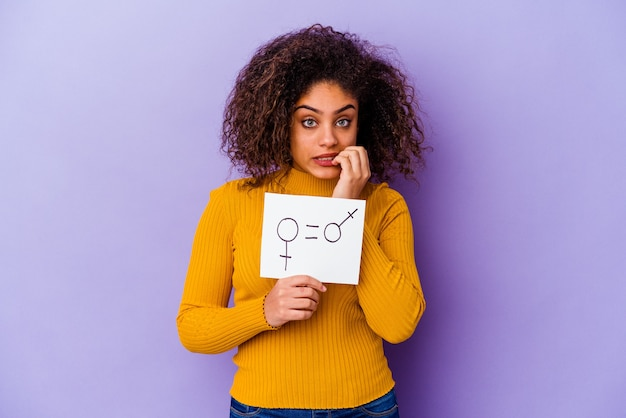 Young african american woman holding a gender equality placard isolated on purple wall biting fingernails, nervous and very anxious.