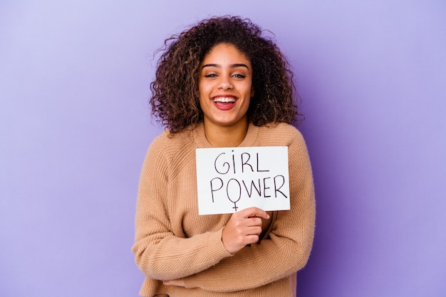 Young african american woman holding a girl power placard isolated on purple background laughing and having fun.