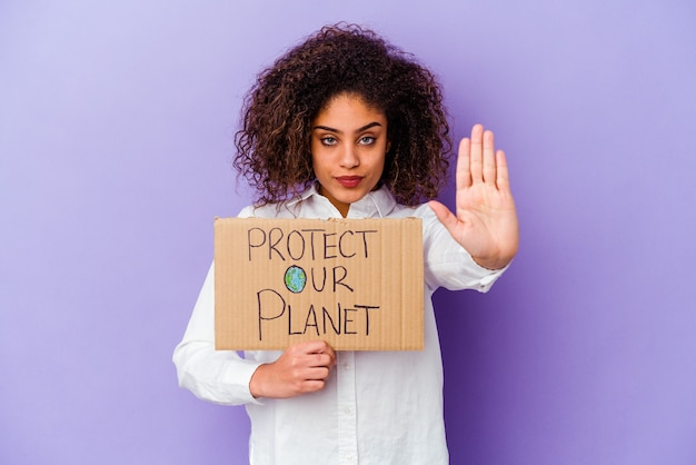 Young african american woman holding a girl power placard isolated