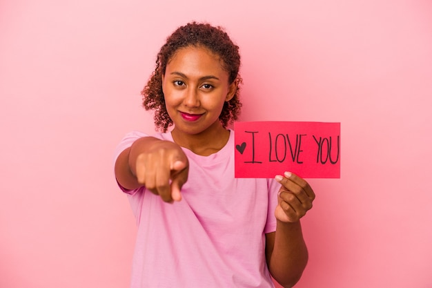 Young african american woman holding i love you placard isolated on pink background