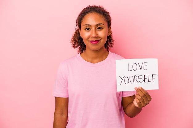 ピンクの背景で隔離のプラカードを保持している若いアフリカ系アメリカ人女性