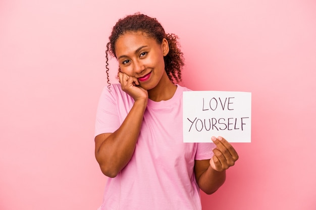 Young african american woman holding love yourself placard isolated on pink background