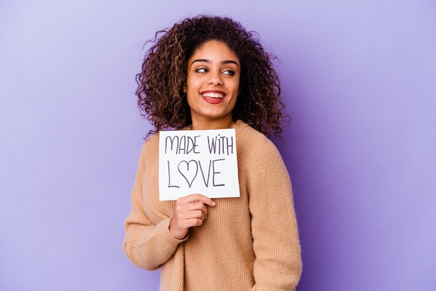 Young african american woman holding a made with love placard isolated on purple looks aside smiling, cheerful and pleasant.