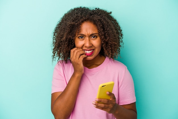 Young african american woman holding a mobile phone isolated on blue background biting fingernails, nervous and very anxious.