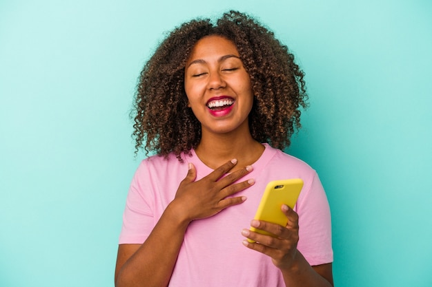 Young african american woman holding a mobile phone isolated on blue background laughs out loudly keeping hand on chest.