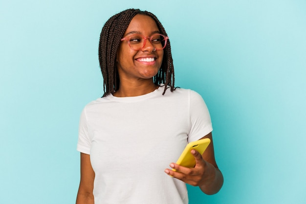 Young african american woman holding a mobile phone isolated on blue background  looks aside smiling, cheerful and pleasant.
