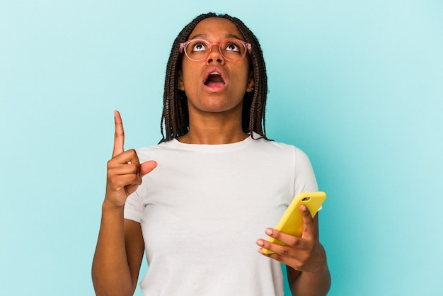 Young african american woman holding a mobile phone isolated on blue background  pointing upside with opened mouth.