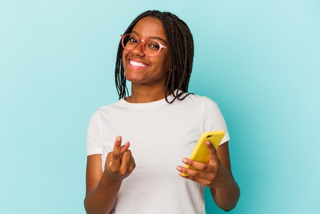 Young african american woman holding a mobile phone isolated on blue background  pointing with finger at you as if inviting come closer.