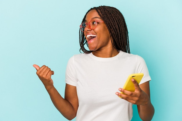 Young african american woman holding a mobile phone isolated on blue background  points with thumb finger away, laughing and carefree.