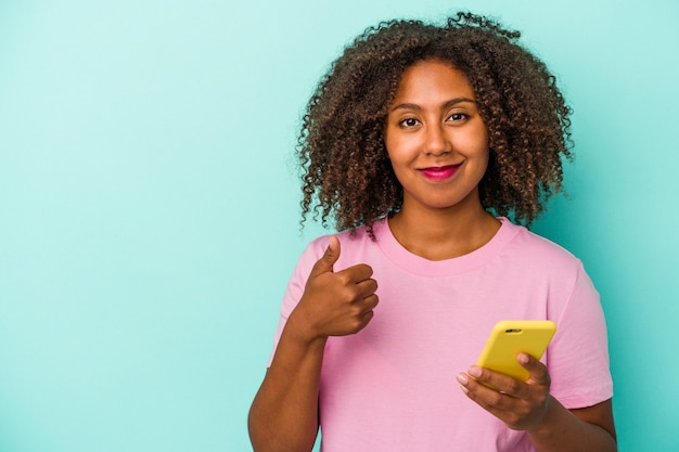 Young african american woman holding a mobile phone isolated on blue background smiling and raising thumb up