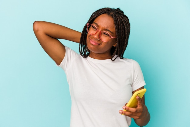 Young african american woman holding a mobile phone isolated on blue background  touching back of head, thinking and making a choice.