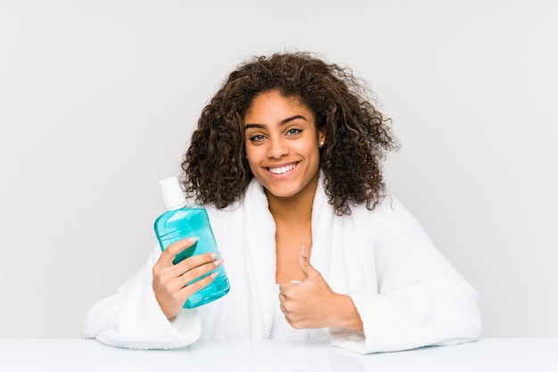 Young african american woman holding a mouth wash smiling and raising thumb up