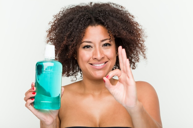 Young african american woman holding mouthwash cheerful and confident showing ok gesture.