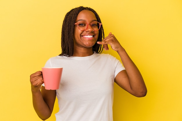 Young african american woman holding a mug isolated on yellow background  showing a mobile phone call gesture with fingers.