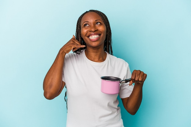 Young african american woman holding pan isolated on blue background showing a mobile phone call gesture with fingers.