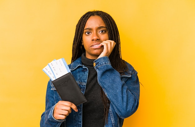 Young african american woman holding a passport isolated biting fingernails, nervous and very anxious.