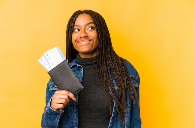 Young african american woman holding a passport isolated dreaming of achieving goals and purposes