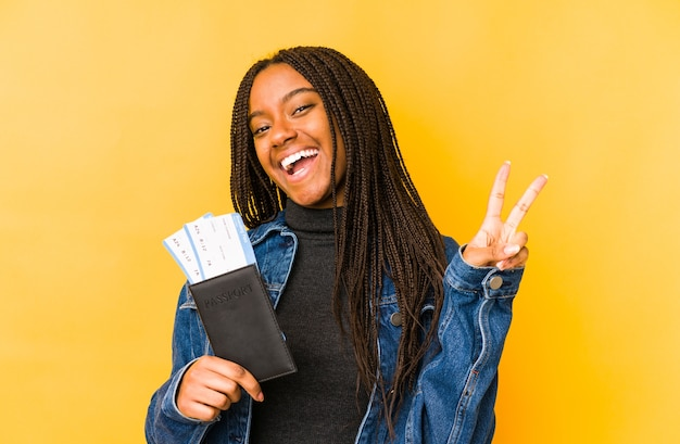 Young african american woman holding a passport isolated joyful and carefree showing a peace symbol with fingers.