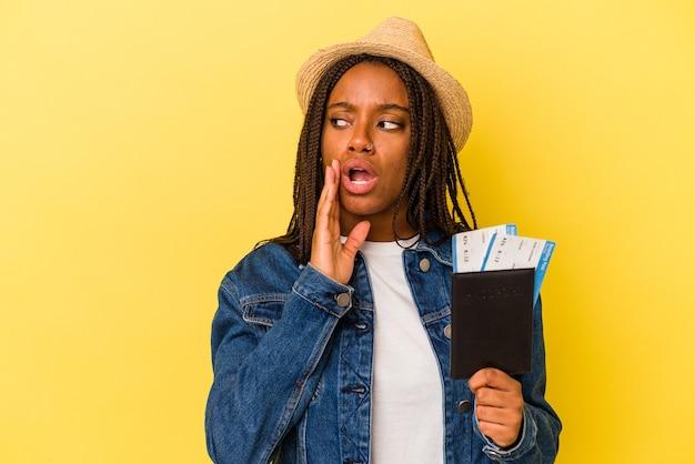 黄色の背景で隔離のパスポートを保持している若いアフリカ系アメリカ人の女性は、秘密のホットブレーキニュースを言って脇を見ています