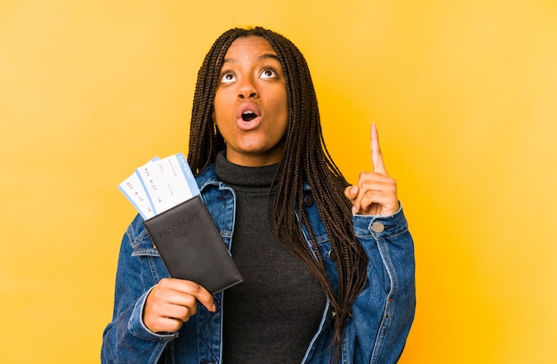 Young african american woman holding a passport isolated pointing upside with opened mouth.