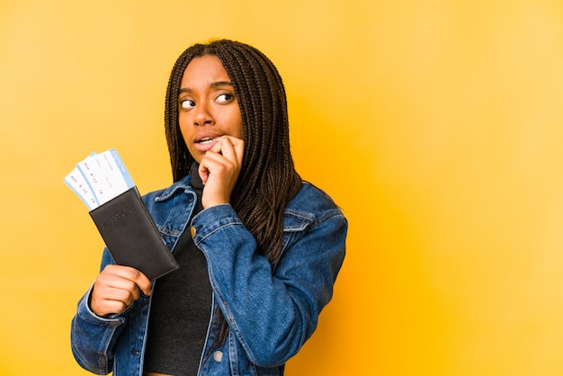 Young african american woman holding a passport isolated relaxed thinking about something looking at a copy space.