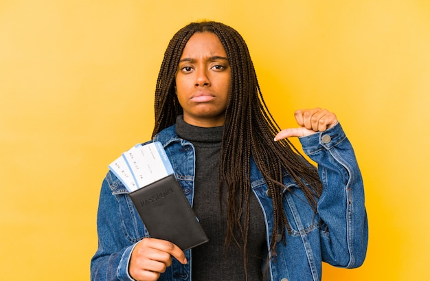 Young african american woman holding a passport showing a dislike gesture, thumb down