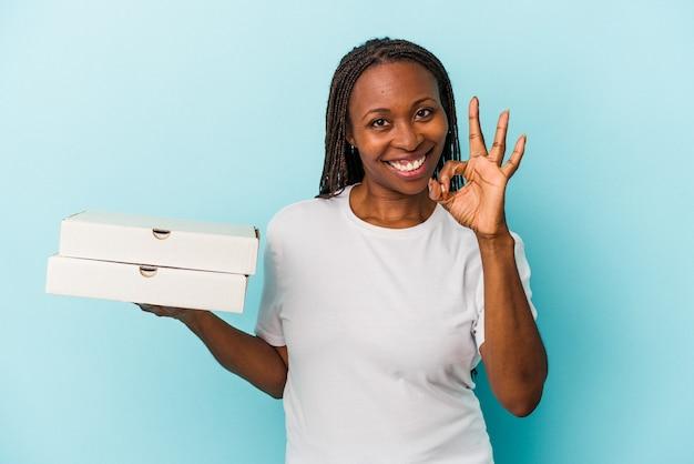 青の背景に分離されたピザを持っている若いアフリカ系アメリカ人女性は、明るく自信を持って大丈夫なジェスチャーを示しています。