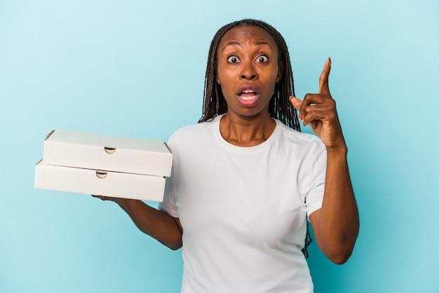 アイデア、インスピレーションの概念を持つ青い背景で隔離のピザを保持している若いアフリカ系アメリカ人女性。
