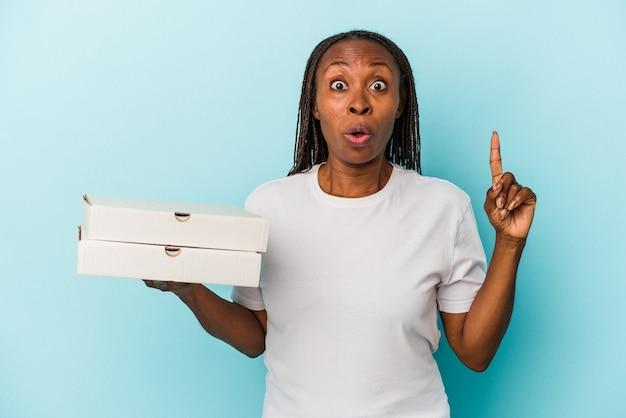 いくつかの素晴らしいアイデア、創造性の概念を持っている青い背景で隔離のピザを保持している若いアフリカ系アメリカ人の女性。