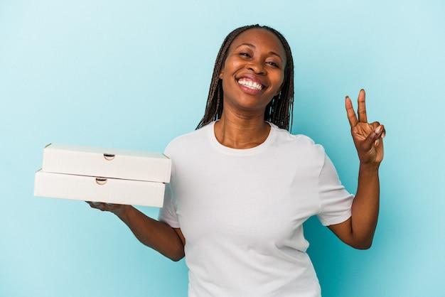 青い背景に分離されたピザを持っている若いアフリカ系アメリカ人の女性は、指で平和のシンボルを示して楽しくてのんきです。