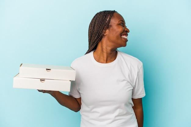 青い背景で隔離のピザを保持している若いアフリカ系アメリカ人の女性は、笑顔、陽気で楽しい脇に見えます。