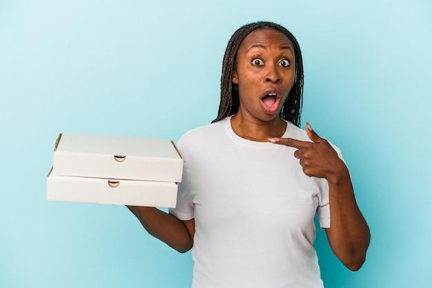 側面を指している青い背景で隔離のピザを保持している若いアフリカ系アメリカ人女性