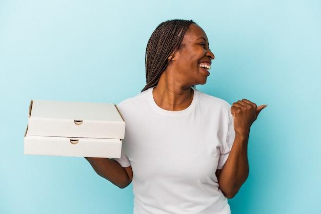 離れて親指の指で青い背景のポイントに分離されたピザを保持し、笑ってのんびりと若いアフリカ系アメリカ人の女性。