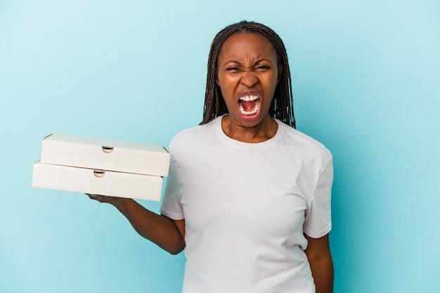 Молодая афро-американская женщина, держащая пиццу, изолированную на синем фоне, кричала очень сердито и агрессивно.