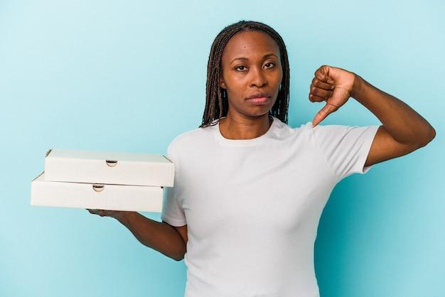 嫌いなジェスチャーを示す青い背景で隔離のピザを保持している若いアフリカ系アメリカ人の女性は、親指を下に向けます。不一致の概念。