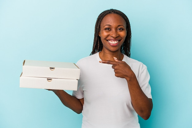 青い背景に分離されたピザを持っている若いアフリカ系アメリカ人の女性が笑顔で脇を指して、空白のスペースで何かを示しています。