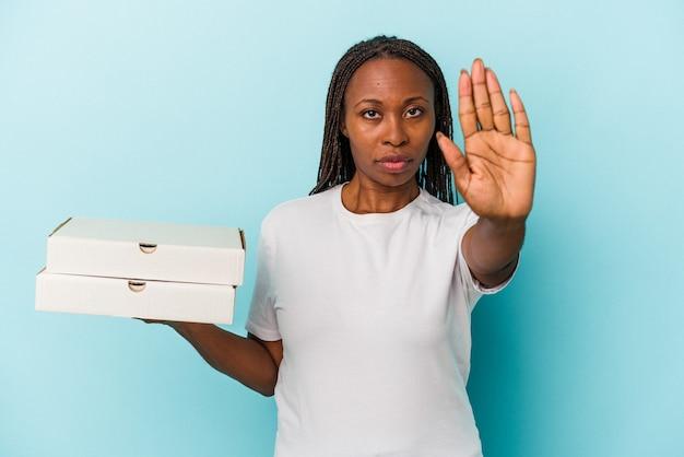 青い背景に分離されたピザを保持している若いアフリカ系アメリカ人女性は、一時停止の標識を示している手を伸ばして立って、あなたを防ぎます。