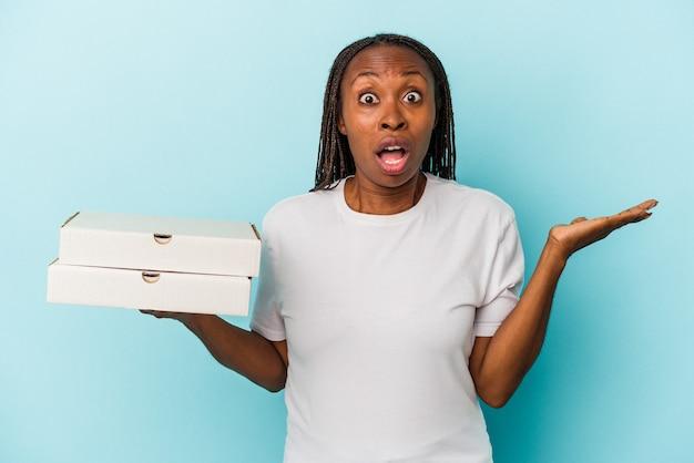 青い背景に分離されたピザを保持している若いアフリカ系アメリカ人女性は驚いてショックを受けました。