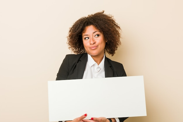 Young african american woman holding a placard smiling confident with crossed arms.