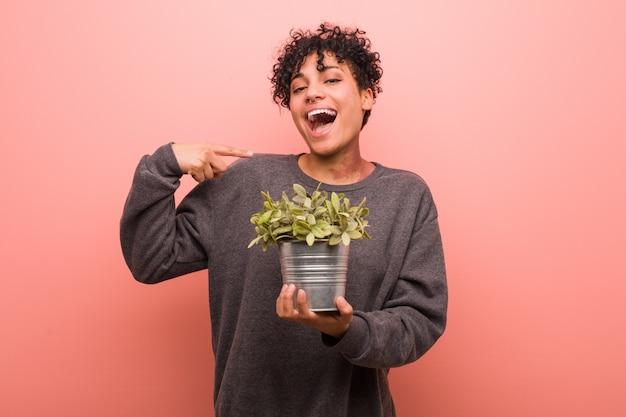 Young african american woman holding a plant showing fist to camera, aggressive facial expression.