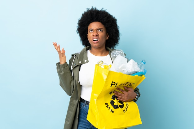 Young african american woman holding a recycle bag on colorful wall stressed overwhelmed