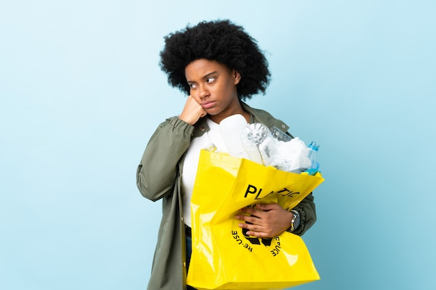 Young african american woman holding a recycle bag on colorful wall with tired and bored expression