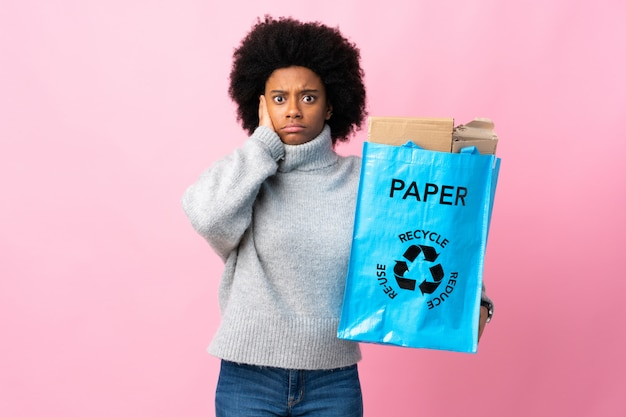 Young african american woman holding a recycle bag isolated on colorful background frustrated and covering ears