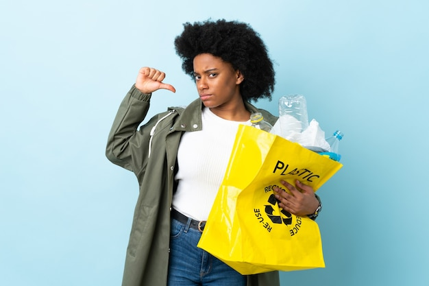 Young african american woman holding a recycle bag isolated on colorful proud and self-satisfied